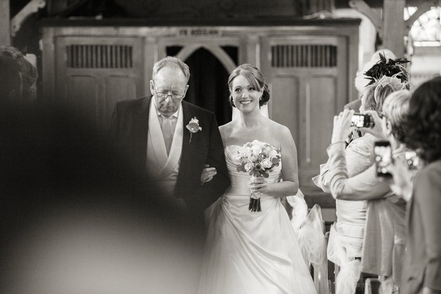 black and white bride and father walking up aisle