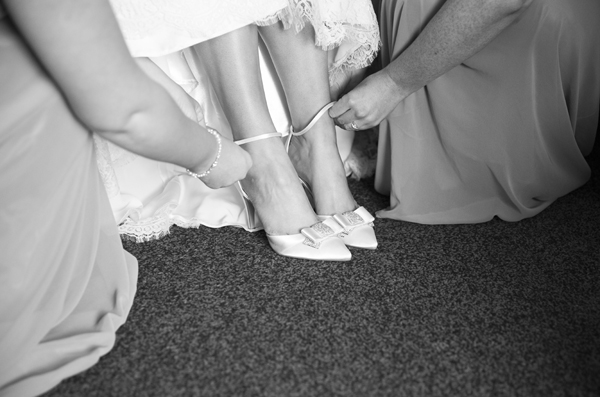 bridesmaids putting on brides shoes