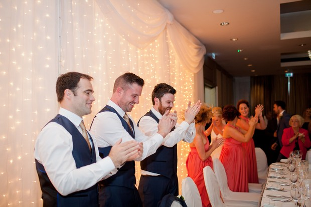 bridal-party-clapping-as-bride-and-groom-make-reception-entrance