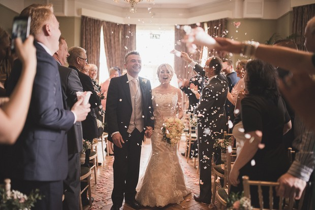 guest-throw-confetti-couple-coming-down-aisle-ceremony (1)
