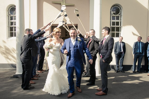 bride-and-groom-ceremony-exit-guests-making-arch-with-hurls