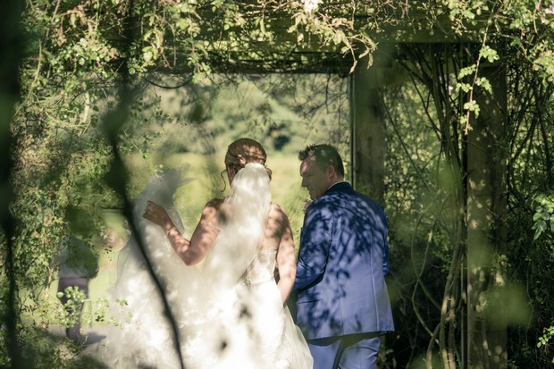 bride-and-groom-walking-through-clontarf-castle-grounds