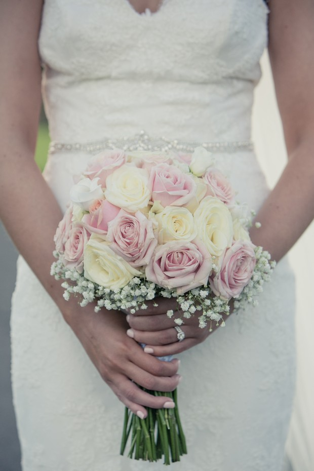 bride-holding-pink-and-cream-rose-bouquet-with-baby's-breath