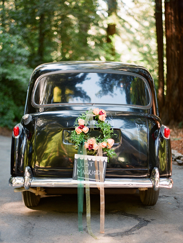 wedding-getaway-car-with-floral-wreath-ribbon-streamers-and-chalk-board-just-married-sign