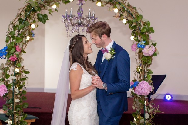 loughrea-hotel-real-wedding-paul-duane-ceremony-bride-and-groom-under-floral-arch