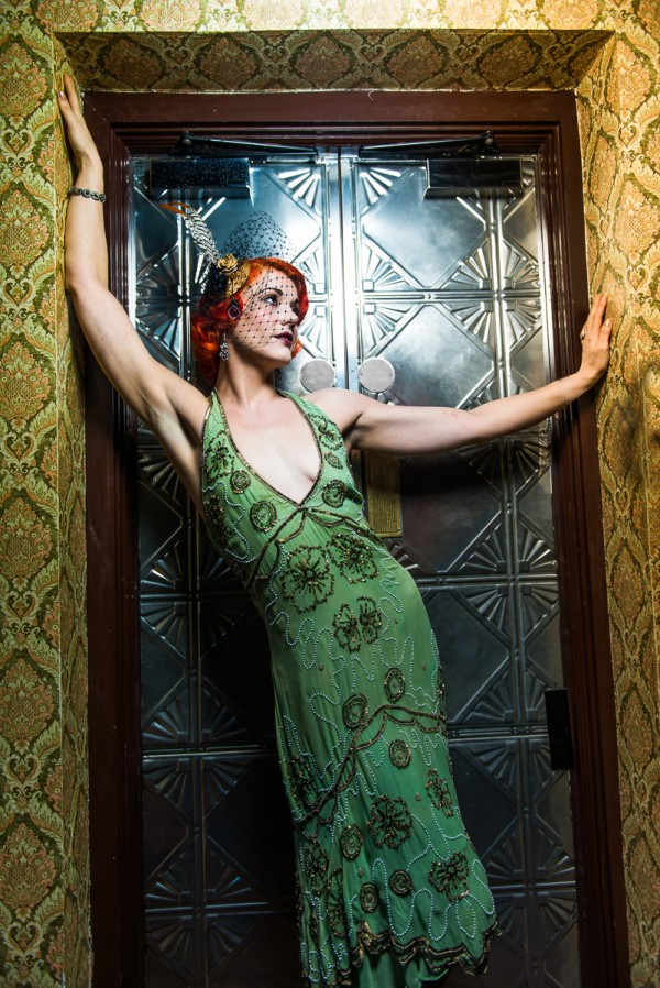 Model with red hair, green and gold flapper dress, vintage jewelery, birdcage