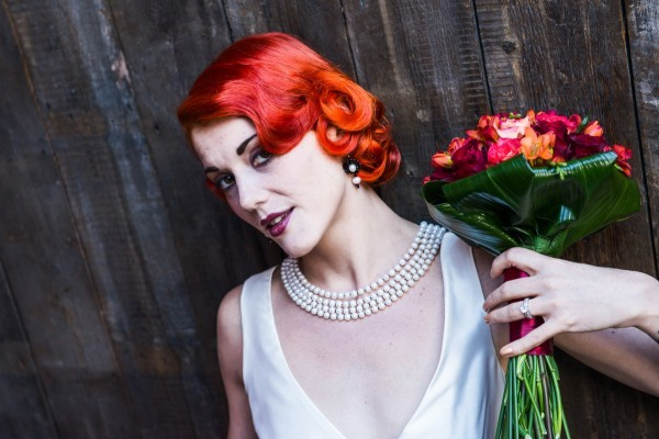 Model with vintage wedding dress, red hair with red bouquet, vintage pearl necklace and black and pearl earrings