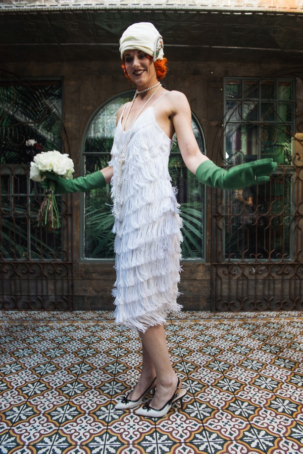 Model with red hair wearing white wedding flapper dress, vintage turban, long green gloves and white bouquet,