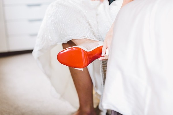 Bride putting on her Louboutin wedding shoes
