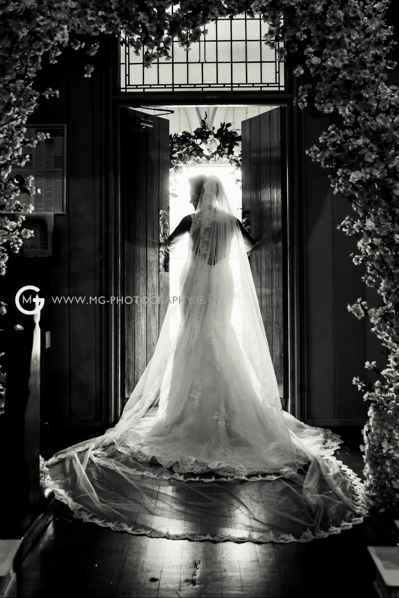 Black and white portrait of a bride at the church door