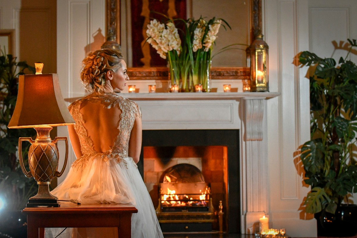 Bride sitting down facing fireplace