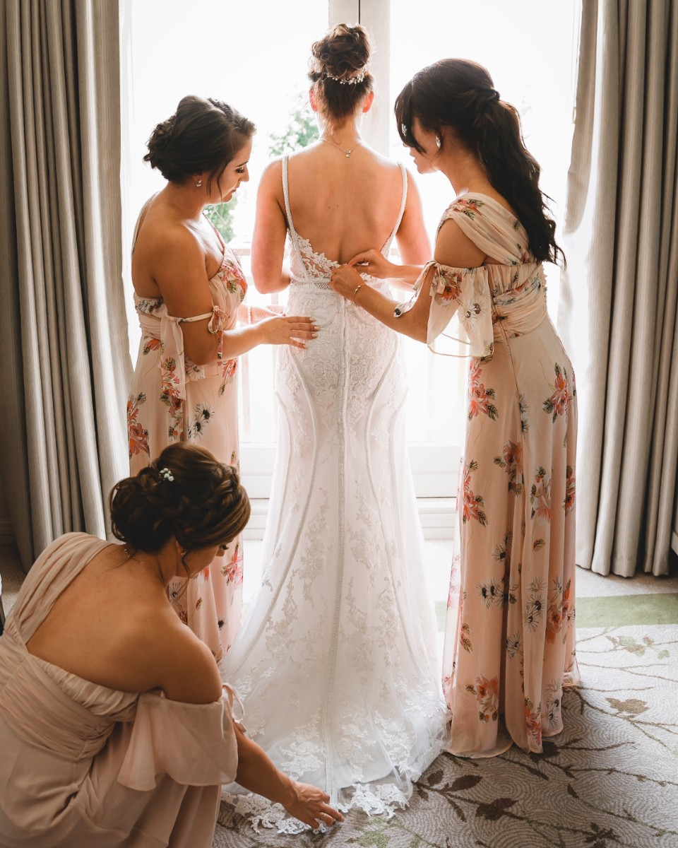Bridesmaids helping bride with her wedding dress
