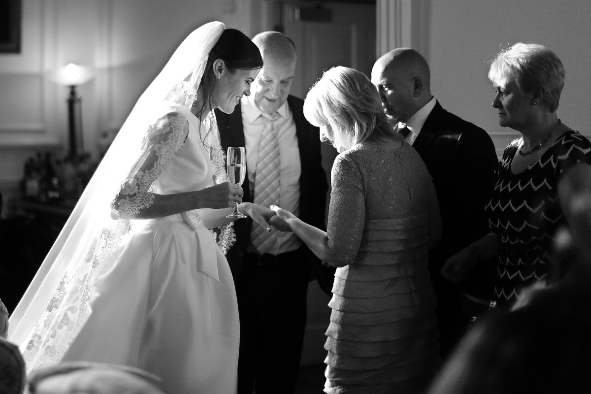 Bride showing her ring to guests, lace veil, Backlight, real wedding, documentary style, natural, reportage, candid, black and white,