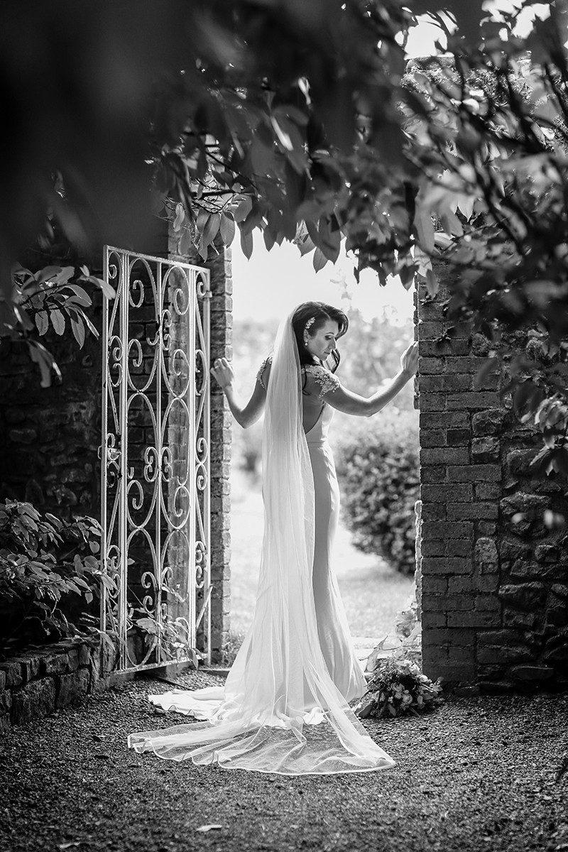 silhouette of bride in gateway, black and white, profile of bride, long lacy veil, forties hair do, backlight
