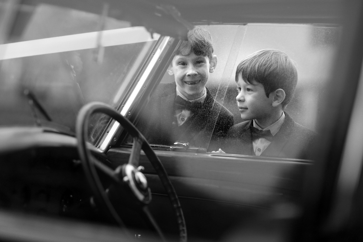 Little boys with vintage car at wedding, creative, pageboys,documentary style, natural, reportage, candid, black and white,