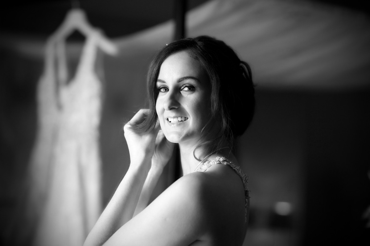 Bride putting on jewellery, earrings, backlight, bride getting ready, real wedding at Carton House