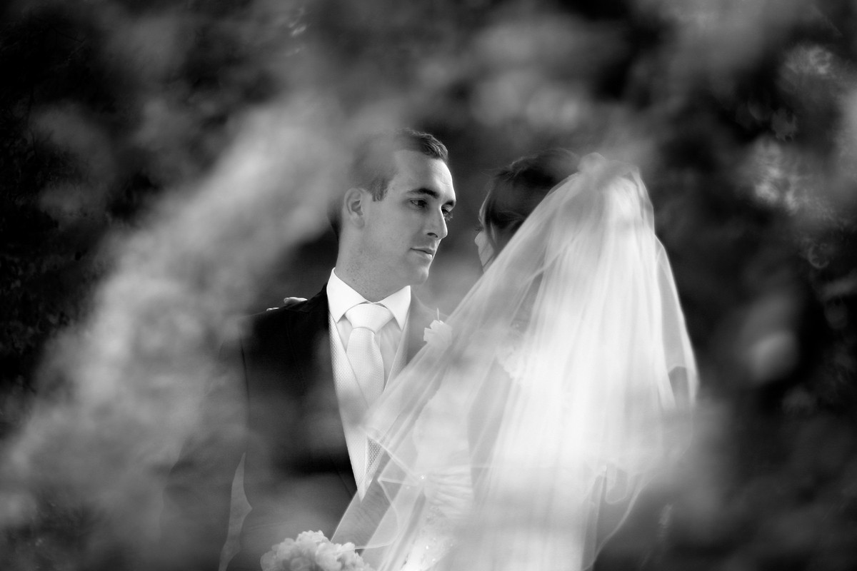 romantic black and white of bride and groom through trees, real wedding Mount Juliet Kilkenny, vintage style