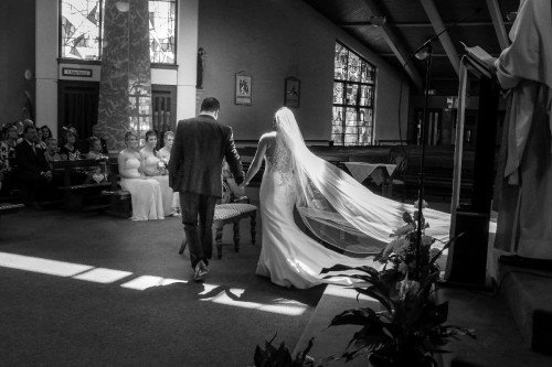 long veil, long train, bride and groom in church, backlight, natural, documentary style,reportage, black & white,