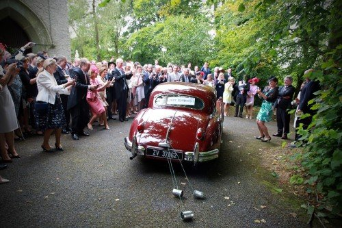 just married vintage car, car and just married cans tied to vintage car, vintage wedding car, vintage jaguar, vintage wedding, guests saying goodbye to newly marrieds, newly weds leaving the church
