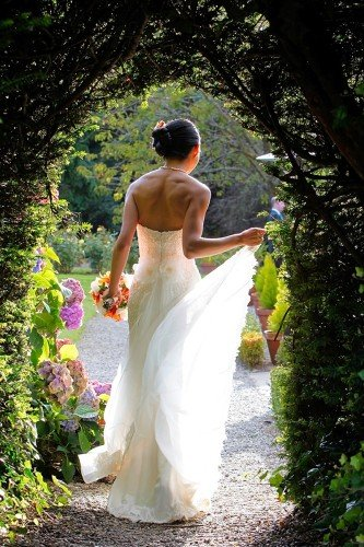bride walking through arch, back light, bridal train, real wedding at Marlfield House