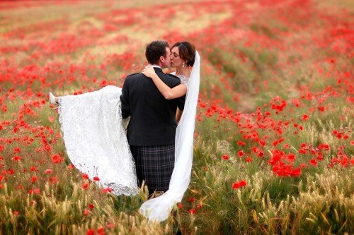 bride and groom in field of flowers, poppy field, Groom carrying Bride, romantic wedding photo in field, real wedding, Barberstown Castle, red flowers