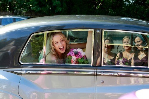 bride greeting bridesmaids, vintage wedding car with bride and bridesmaids, pink bouquet, purple bridesmaid dresses