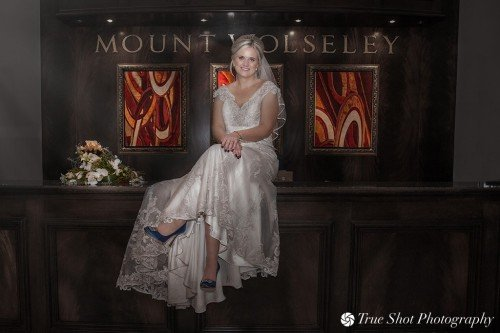 Bride sitting on top of bar at Mount Wolseley