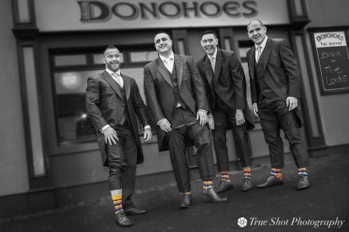 Groom and best men before the wedding showing off their socks
