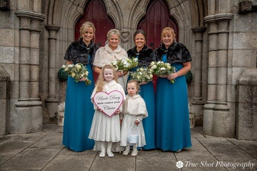 Bride, bridesmaids and flower girls outside St. Aidans church
