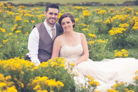 Bride and Groom sitting in a field, Tara Donoghue photography