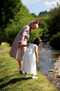 Grandmother and grandaughter at wedding, flowergirl, by the river